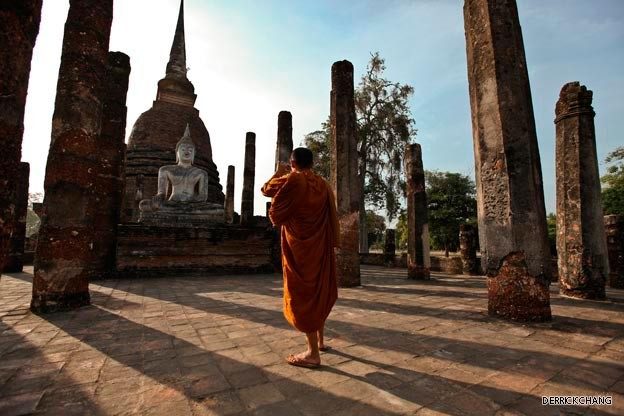 A Buddhist monk takes a photo of the seated Buddha at Wat Trapang Ngoen.jpg